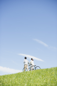 草原で自転車を押すカップル