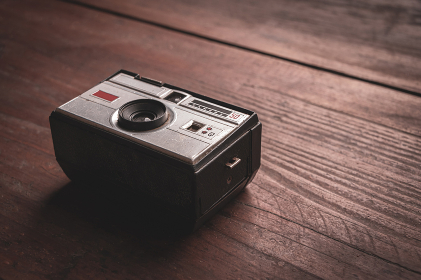 Old and worn photo camera from the 60s on rustic wooden table