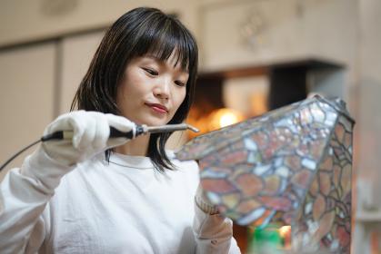 ステンドグラスのランプを作る女性