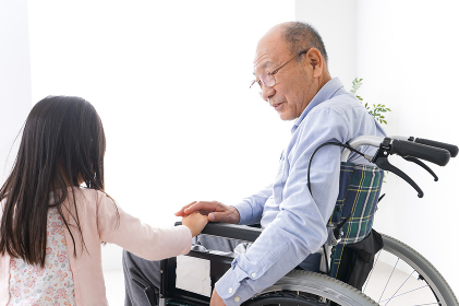 車椅子に乗る高齢男性と女の子