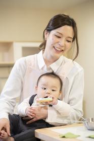 赤ちゃんを抱えて遊ぶ保育士の女性