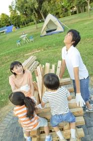 キャンプファイヤーを組む家族