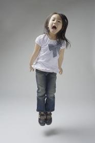 ジャンプする6歳のジーパンをはいた女の子