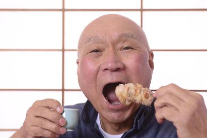 焼き鳥を食べながら日本酒を飲む日本人シニア男性