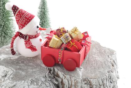 雪をかぶった切り株に置かれたサンタクロースや雪だるまやトナカイが運んできたクリスマスプレゼント