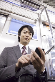 電車内でスマートフォンを操作するビジネスマン