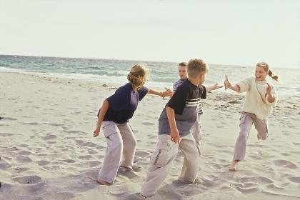 Strandszene, Portrait, 2 Maedchen und 2 Jungen im Alter von 10 -12 Jahren bei der Uebergabe des Stabes bei einem Staffellauf barfuss im Sand
