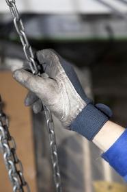チェーンブロックを引く労働者の手