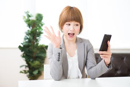 スマホを見る女性 ビジネス 考える