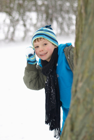 Boy hiding behind tree with snowball