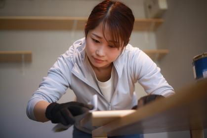 紙やすりで材木を磨く女性