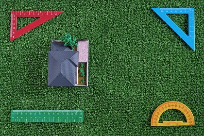 緑の人工芝に置いたミニチュアの家と三角定規などの文房具