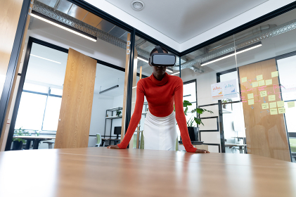 African american businesswoman leaning on desk and using vr headset in meeting room. business in a modern office.