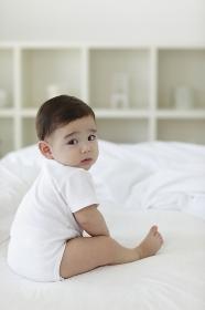 ベッドの上でお座りをして振り返る赤ちゃん