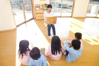 紙芝居に聞き入る幼稚園児5人の後姿