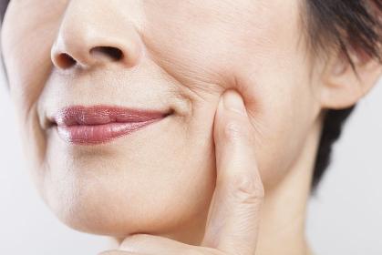 頬の張りを確かめるシニア女性