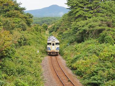 岩木山を背景に走る五能線の普通列車