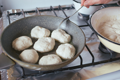 Yeast pancakes are fried in oil in frying pan on stove