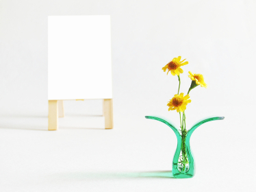 プラスチッククリップに挟んだ黄色い花と白色の立て看板のコピースペース