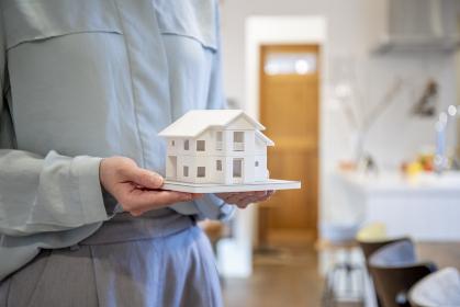 家の模型を持つ若い女性の手元