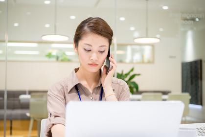真剣な表情で仕事をする会社員(女性・電話・パソコン)