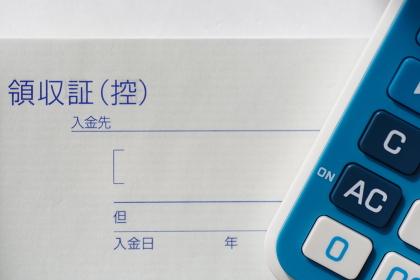 領収書と電卓(経費のイメージ素材)