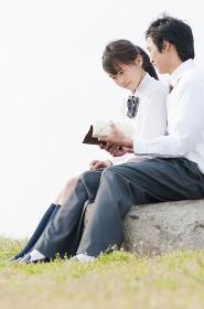 本を読む高校生カップル