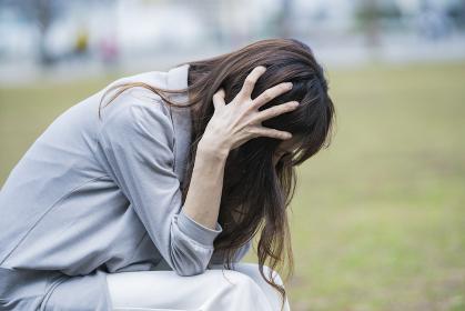 ストレスが原因で頭を抱えるビジネスウーマン
