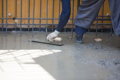 コテでコンクリートの表面を仕上げる職人