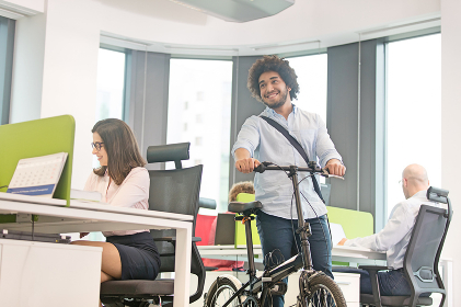 Young businessman walking with bicycle while colleagues working in office