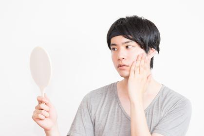 鏡を見る男性(男性のフェイスケア・美容イメージ)