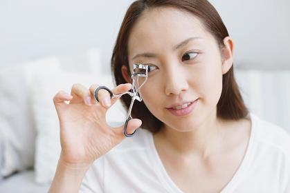 リビングでメークアップしている若い日本人女性
