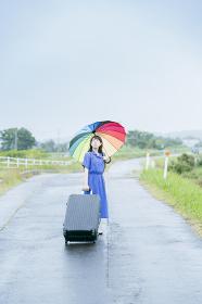スーツケースとカラフルな傘を持つ女性