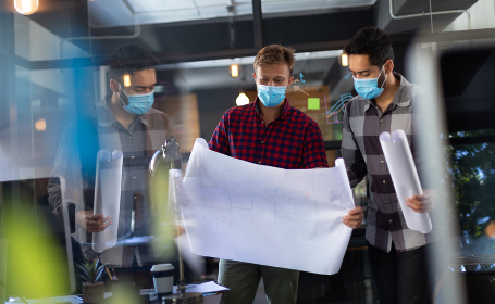 Diverse male colleagues wearing masks in disucssion holding architectural plans in office. seen through glass wall. hygiene in workplace during coronavirus covid 19 pandemic.