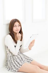 部屋でタブレットコンピューターを見る女性 考える