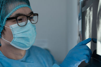 Mixed race male surgeon in operating theatre wearing face mask looking at screen. medicine, health and healthcare services during coronavirus covid 19 pandemic.