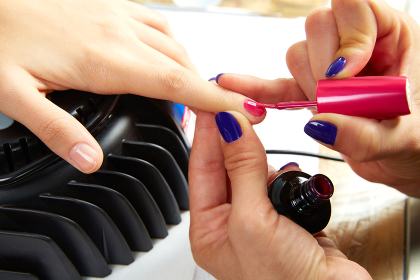 Nails painting with UV dry lamp in blue light woman hands at nail salon