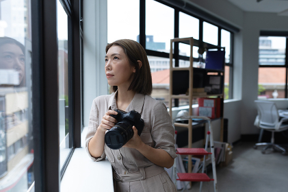 Asian businesswoman holding camera looking through window in creative office. social distancing in workplace during covid 19 pandemic.