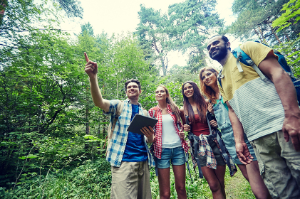 happy friends with backpacks and tablet pc hiking