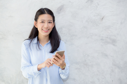 Beautiful young asian woman talking phone and smile standing on
