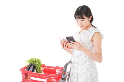 スーパーで食料品を調べる若い女性