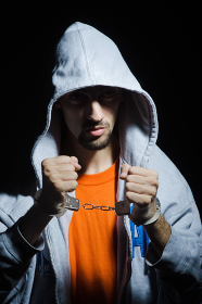 Young criminal with handcuffs