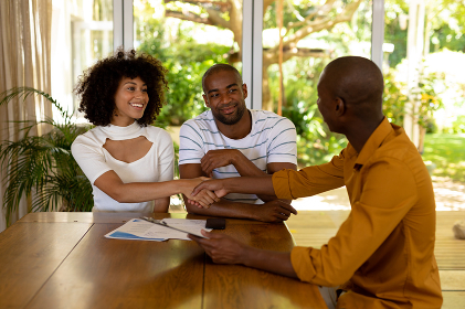 Front view of a mixed race couple sitting in their living room shaking hands with an African American male financial adviser,  with sun shining in the garden outside