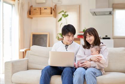 ソファでノートパソコンを見るアジア人ファミリー