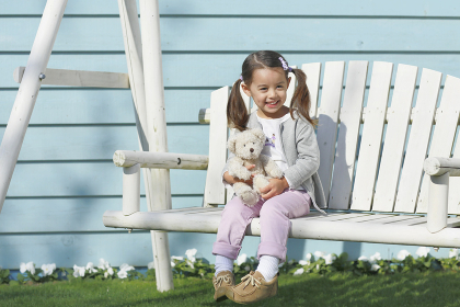 庭の白いブランコに座る小さな女の子