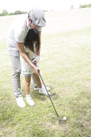 ゴルフをする親子