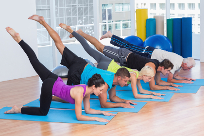 People exercising on fitness mats at gym