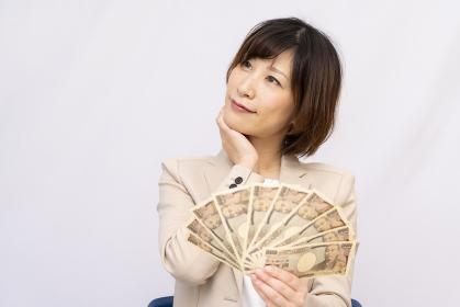 お金の使い道に悩む女性【2020
