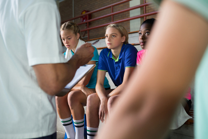 Volleyball coach talking to female players
