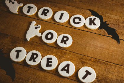 Cookies with trick or treat text by spooky decorations on wooden table